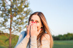Surprised young woman with hands over her mouth outdoor.  Stock Image