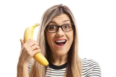 Surprised young woman holding a banana stock images