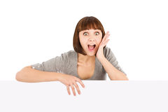 Surprised young woman holding blank billboard Royalty Free Stock Image