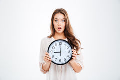 Surprised young woman holding clock Stock Photos