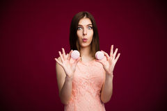 Surprised young woman holding cookies Stock Photos