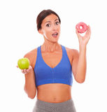 Surprised young woman holding food temptations Royalty Free Stock Photos