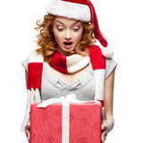 Surprised young woman holding gift on white. Surprised young caucasian woman in santa hat holding gift isolated on white Royalty Free Stock Photography