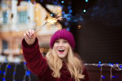 Surprised young woman holding glowing bengal lights at the Chris. Surprised blonde woman holding glowing bengal lights at the Christmas tree. Blur effect Stock Image