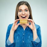 Surprised young woman holding golden credit card. Isolated portrait Royalty Free Stock Image