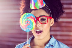 Surprised young woman holding a lollipop against her face Royalty Free Stock Photography