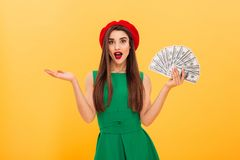 Surprised young woman holding money. Looking camera. stock photo