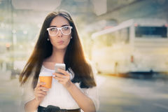 Surprised Young Woman Holding Smartphone and Coffee Cup Stock Photo
