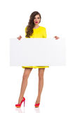 Surprised Young Woman Holding White Poster Stock Photography