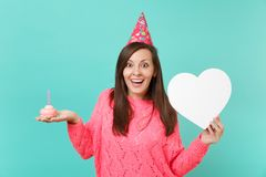 Surprised young woman in knitted pink sweater, birthday hat holding cake with candle, white heart with copy space. Isolated on blue turquoise background. People royalty free stock images