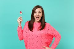 Surprised young woman in knitted pink sweater keeping mouth wide open, hold in hand watermelon lollipop isolated on blue stock images