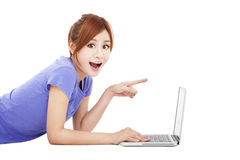 Surprised young woman with laptop. Surprised young asian woman with laptop and pointing Stock Images
