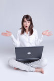 Surprised Young woman with laptop on the floor Stock Photography