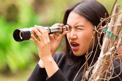 Surprised young woman looking through black monocular in the forest in a blurred background.  Royalty Free Stock Photos