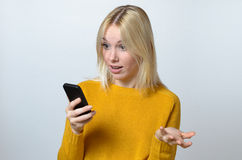 Surprised Young Woman Looking at her Mobile Phone Stock Photo