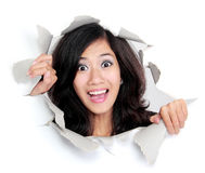Surprised young woman looking through a hole Stock Image