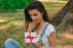 Surprised young woman with open gift in her hands. At the park Royalty Free Stock Photo