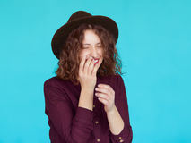 Surprised young woman over blue turquoise background. Laughing young woman wearing violet shirt and stylish hat. Happy hipster girl with eyes closed covering her Stock Image