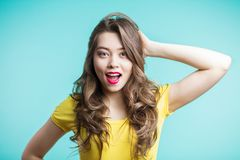 Surprised young woman over bluebackground. Looking at camera stock photography