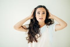 Surprised young woman shouting over white background. Looking at camera Royalty Free Stock Image