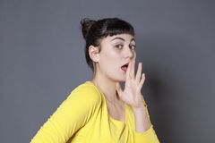 Surprised young woman playing confidential and taboo with face expression Royalty Free Stock Photography
