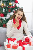 Surprised young woman with present boxes near christmas tree Royalty Free Stock Photography