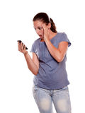 Surprised young woman reading on cellphone Royalty Free Stock Photos