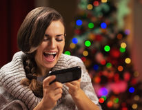 Surprised young woman reading sms near christmas tree Stock Photos