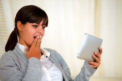 Surprised young woman reading the tablet pc screen Stock Image