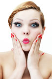Surprised young woman with red plaited hair and red lips touching her face. Stock Photos