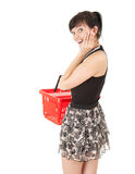 Surprised young woman with red shopping basket Royalty Free Stock Photography