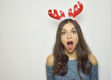 Surprised young woman with reindeer horns on her head with mouth open on white background. Christmas concept Stock Photos