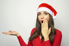 Surprised young woman with Santa Claus hat showing your product on her hand looking at camera. Copy space. Stock Photo