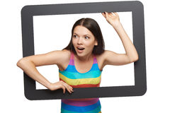 Surprised young woman scrambling out of tablet frame Stock Photos