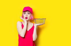 Surprised young woman with shopping bag. Portrait of surprised young woman with shopping bag on the wonderful yellow studio background Royalty Free Stock Photo