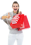 Surprised young woman with shopping bags showing thumbs up Stock Images