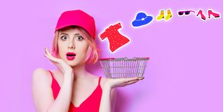 Surprised young woman with shopping basket. Portrait of surprised young woman with shopping basket and clothes on the wonderful purple studio background Stock Photography