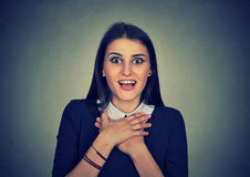 Surprised young woman shouting looking at camera. Surprised young woman shouting over gray background. Looking at camera Royalty Free Stock Images