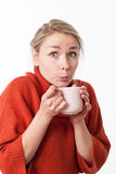 Surprised young woman sipping a hot tea,coffee,chocolate Stock Photos