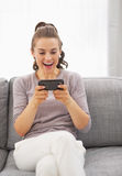 Surprised young woman sitting on sofa and reading sms Royalty Free Stock Photography