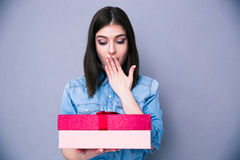 Surprised young woman standing with gift Royalty Free Stock Photo