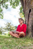 Surprised young woman studying on wireless tablet in park Stock Photography