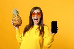 Surprised young woman in sunglasses hold pineapple fruit, mobile phone with blank empty screen isolated on yellow orange. Background. People vivid lifestyle royalty free stock images