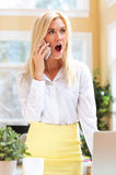 Surprised young woman talking on the phone Royalty Free Stock Photography