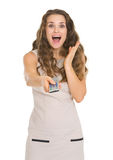 Surprised young woman with tv remote control Stock Image