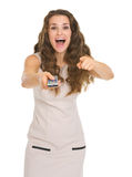 Surprised young woman with tv remote control Stock Photo