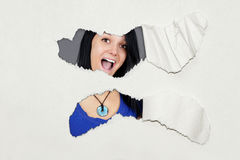 Surprised young woman under ripped paper. Very surprised young woman under ripped thick textured paper, fun advertisement Royalty Free Stock Images