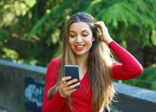 Surprised young woman using smart phone outdoors. Excited urban girl using new mobile phone app in city park royalty free stock photos