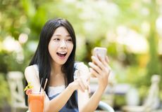 Surprised young woman  watching smart phone Royalty Free Stock Images
