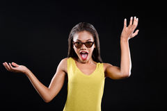 Surprised young woman is wearing glasses. Shocked girl in sunglasses is raising her hands. She is isolated on black background Royalty Free Stock Images